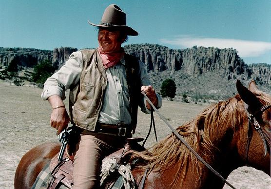 John Wayne in The UNdefeated on horse with gun